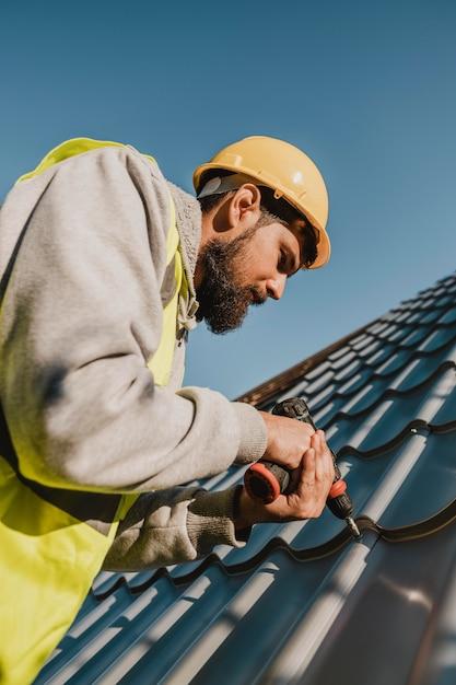 ドリルロービューで屋根に取り組んでいる男 無料写真