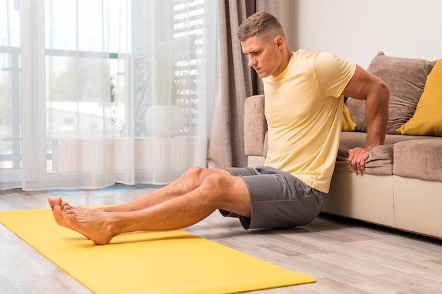 ソファを使用して自宅で運動する男 無料写真