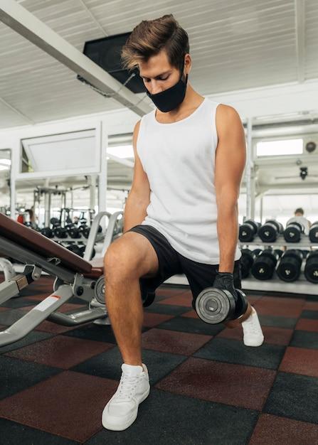 医療マスクでジムで運動する男 Premium写真