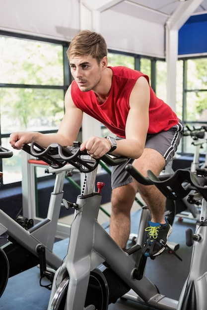 Man working out on exercise bike at spinning class Premium Photo