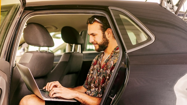 Man working remotely on back seat of car Free Photo