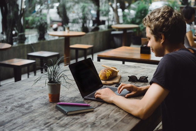 Man working with a laptop in a cafe on a wooden table Free Photo