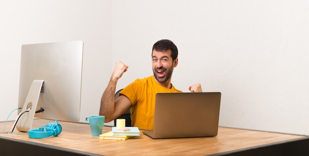 Man working with laptot in a office celebrating a victory Premium Photo