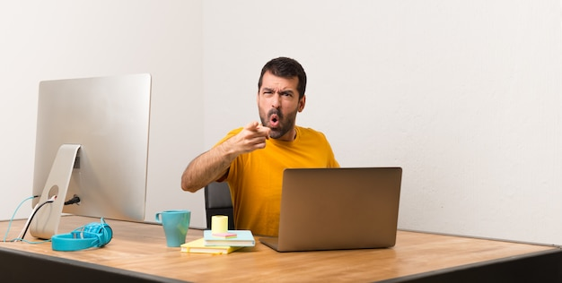 Man working with laptot in a office frustrated by a bad situation and pointing to the front Premium Photo