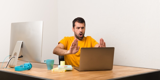 Man working with laptot in a office making stop gesture for disappointed with an opinion Premium Photo