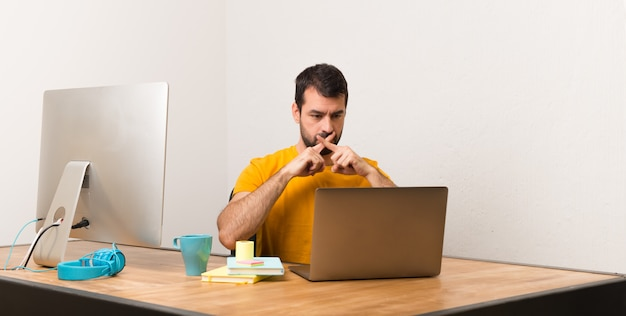 Man working with laptot in a office showing a sign of silence gesture Premium Photo