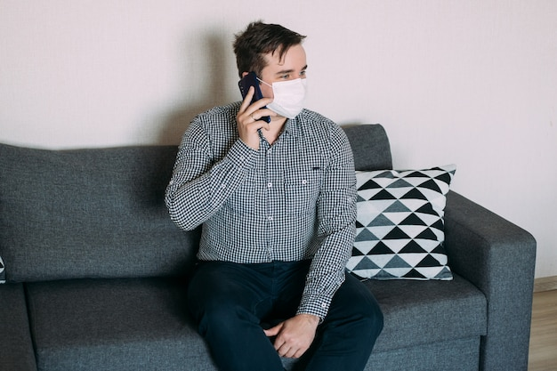 Man working with smartphone working from home office wearing mask Premium Photo