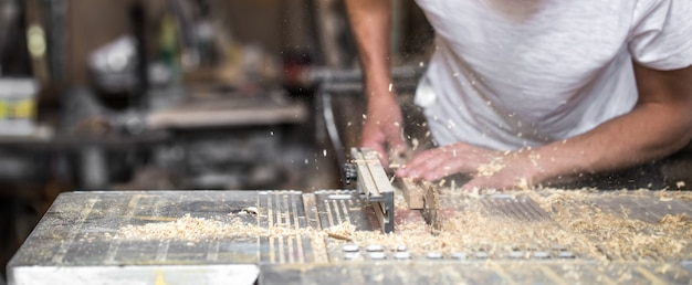 Un uomo che lavora con prodotti in legno sulla macchina, primo piano Foto Gratuite