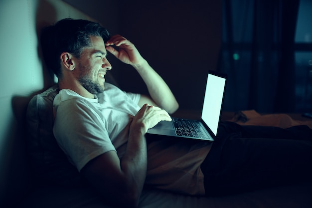 A man works on a laptop in bed, a beloved woman sleeps, night work, treason Premium Photo