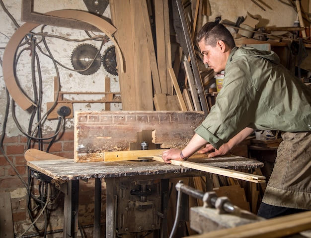 A man works on the machine with the wooden product manufacturing Free Photo