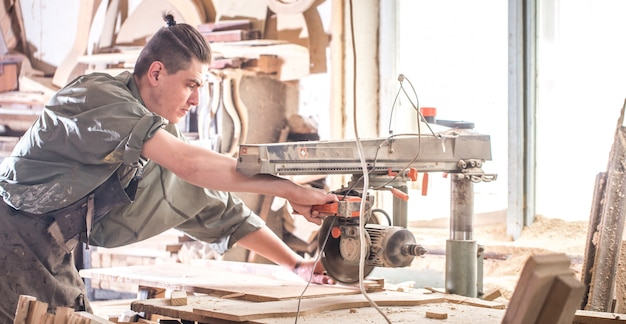 A man works on the machine with the wooden product Free Photo
