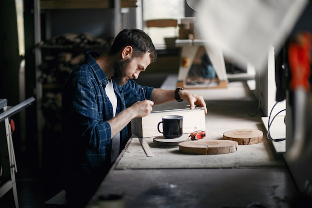 Man in the workshop with a wood Free Photo