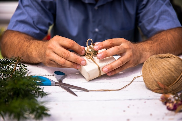 Man wrapping a cute gift Free Photo