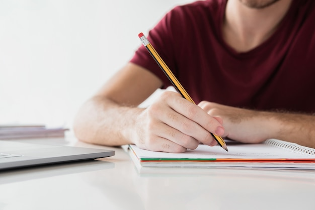 Man writing on his notepad with pencil Free Photo
