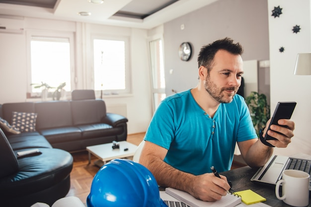 Man writing notes and holding smart phone Premium Photo