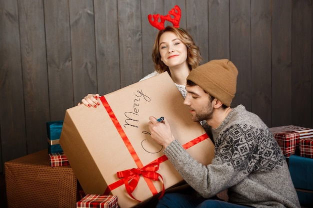 Человек, писать на подарочной коробке счастливого рождества, сидя с подругой Бесплатные Фотографии