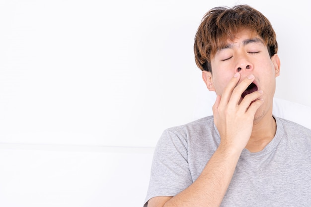 Man yawning and covering mouth with hand Premium Photo