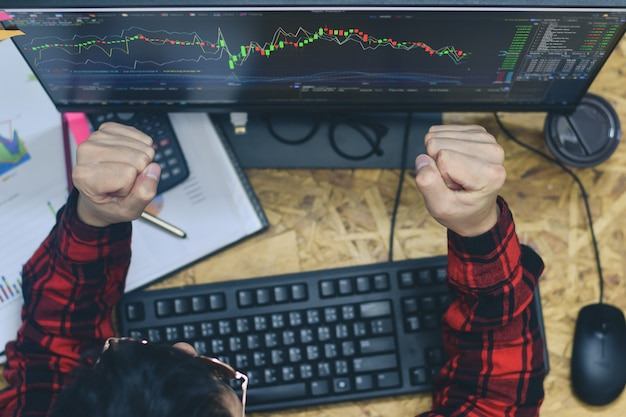 Man yeah we did it. triumphing delighted and joyful when be able to live off their profits from trading at home office in while trading forex or stocks market online investment at night time Premium Photo