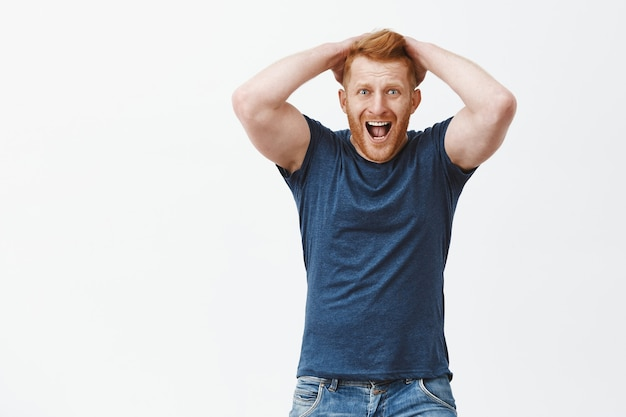 Man yelling from regret and shock. handsome mature redhead guy in despair, touching hair, screaming and staring shocked and devestated, feeling disappointment over gray wall Free Photo