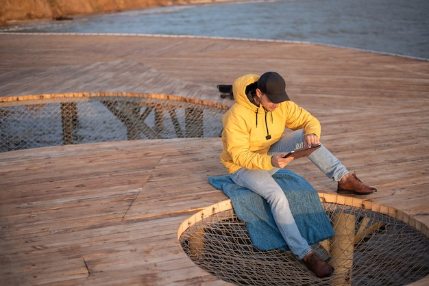 Man in a yellow raincoat and a black cap sits on a wooden pier, uses a tablet Premium Photo