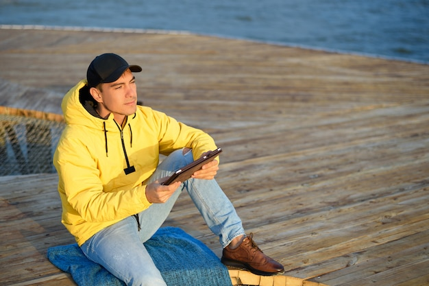 Man in a yellow raincoat and a black cap sitting on the dock with a tablet looking at the dawn Premium Photo