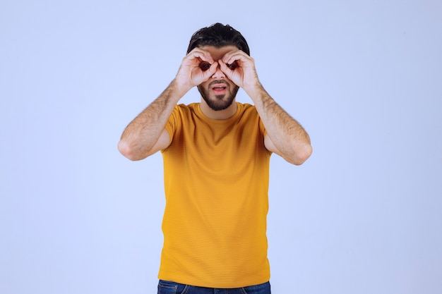 Man in yellow shirt looking ahead. Free Photo