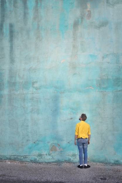 Man in yellow t-shirt looking up on a wall Premium Photo