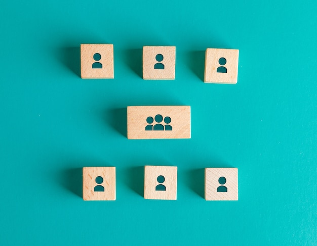 Management structure concept with people icons on wooden blocks on turquoise table flat lay. Free Photo