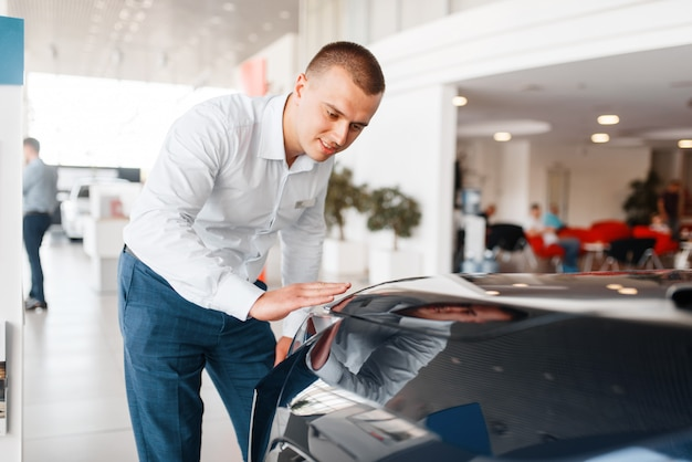 Manager checks the quality of new car paintwork in showroom. male customer buying vehicle in dealership, automobile sale, auto purchase Premium Photo
