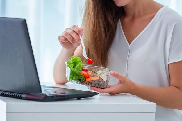 점심 시간 동안 직장에서 도시락 상자에서 식사를하는 관리자. 직장에서 컨테이너 식품 프리미엄 사진