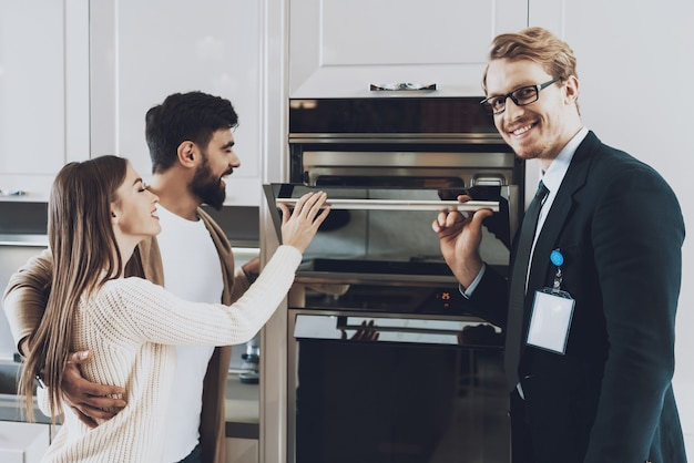 Manager is showing built-in stove to couple clients. Premium Photo