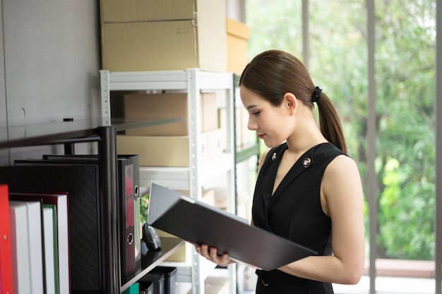 A manager is standing next to shelves in office. she is in black suit and holding a folder. Premium Photo