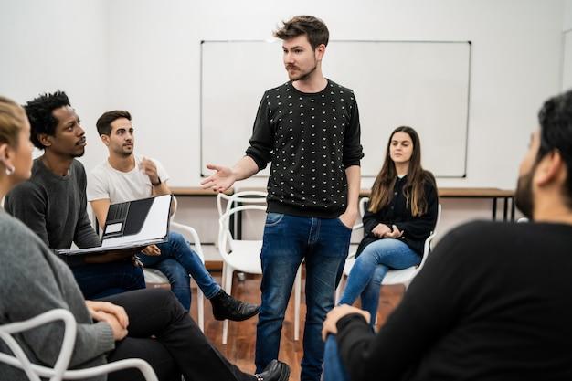 사무실에서 창의적인 디자이너 그룹과 브레인 스토밍 회의를 주도하는 관리자. 리더 및 비즈니스 개념 무료 사진