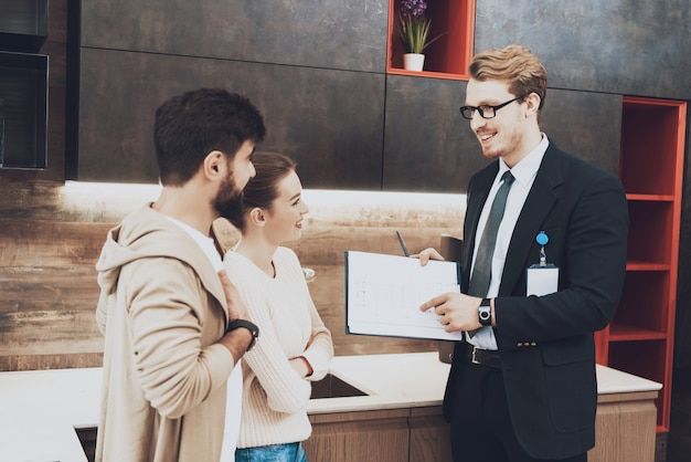Manager in suit is showing kitchen blueprints to couple Premium Photo