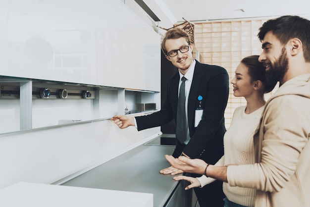 Manager in suit is showing new kitchen to couple Premium Photo
