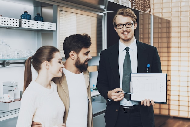 Manager in suit looking at camera showing blueprints Premium Photo