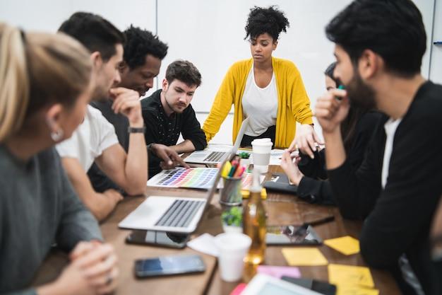 사무실에서 창의적인 디자이너 그룹과 브레인 스토밍 회의를 선도하는 관리자 여자. 지도자와 비즈니스 개념. 프리미엄 사진