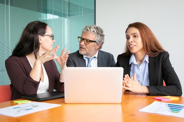 オープンラップトップを使用してテーブルで会議を行い、上司とアイデアを議論および共有するマネージャー。 無料写真