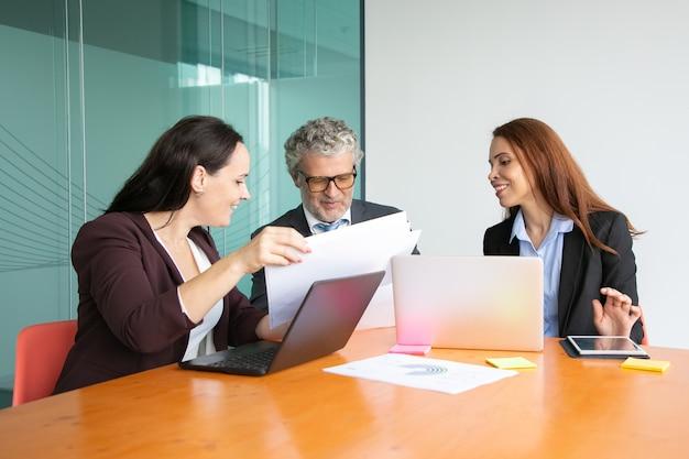 Manager che presentano rapporti cartacei al capo. uomo dai capelli grigi in vestito e due donne di affari che esaminano insieme i documenti. Foto Gratuite