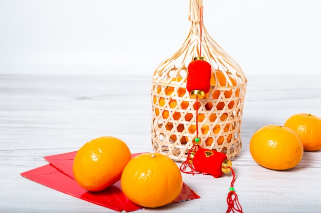 Mandarin oranges with chinese new year red packets and a red lamp Premium Photo