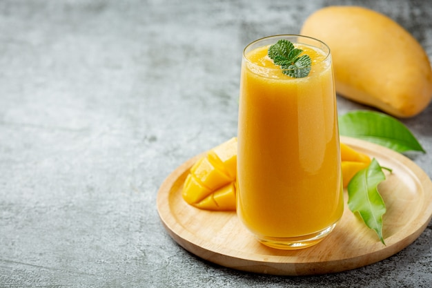 Mango juice in the glass on dark surface Free Photo