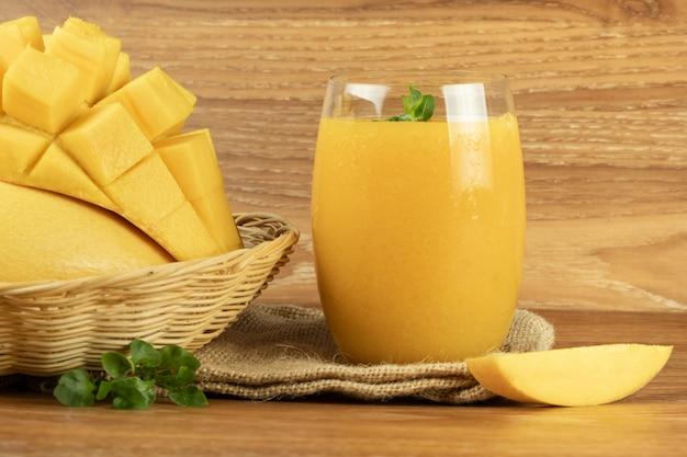 Mango smoothie juice. wooden background. Premium Photo