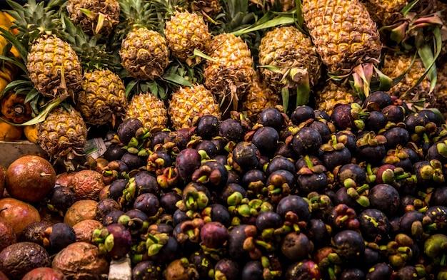 タイのカウンターマーケットでマンゴスチンとパイナップル 無料写真