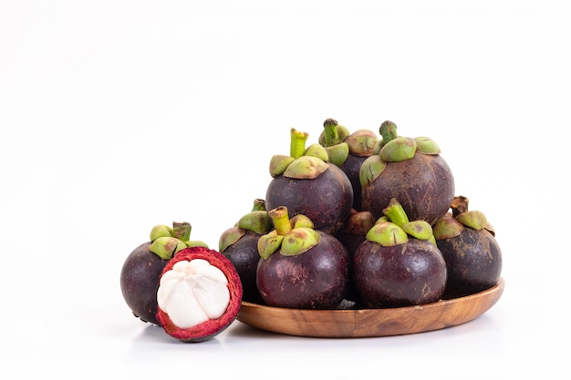 Mangosteen and cross section showing the thick purple skin and white on white Premium Photo