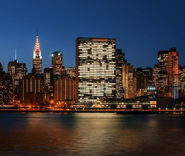 Манхэттен ночью. горизонт нью-йорка с огнями и отражениями. Premium Фотографии
