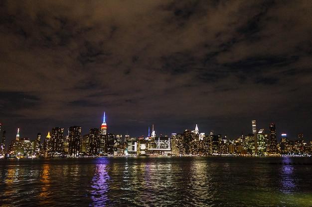 Манхэттен ночью выстрелил издалека с отражением реки Бесплатные Фотографии