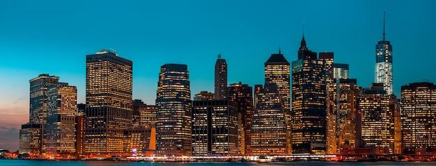 Манхэттен ночью с огнями и отражениями. горизонт нью-йорка Premium Фотографии