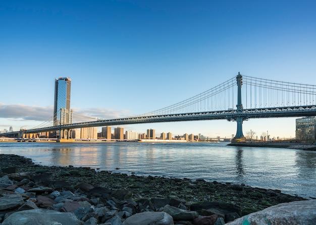 Манхэттенский мост с горизонтом нижнего манхэттена утром при ярком свете над ист-ривер в нью-йорке. Premium Фотографии