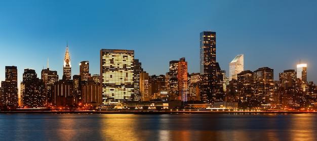 Манхэттен. поздний вечер панорама горизонта нью-йорка с огнями и отражениями. Premium Фотографии