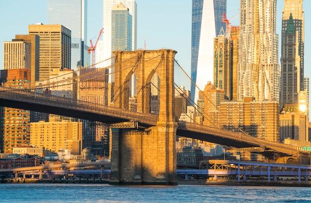 Горизонт манхэттена с бруклинским мостом на переднем плане и башней свободы на заднем плане. Premium Фотографии